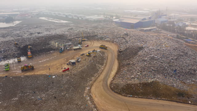aerial hyper lapse or time lapse of large stack garbage dump - dump truck stock videos & royalty-free footage