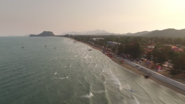 Aerial hyperlapse of a sandy beach from above with kiteboarders riding on the stunning blue water in Pranburi, Thailand