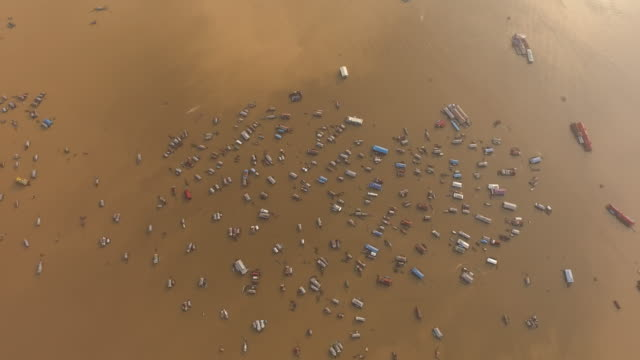 vídeos de stock e filmes b-roll de aerial hyperlapse of floating village with a bird's eye view of the muddy brown waters and its floating houses - condensação