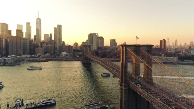 vidéos et rushes de hyperlapse aérienne. la vue panoramique de manhattan downtown et brooklyn bridge de brooklyn heights, sur l'east river au coucher du soleil. - pont
