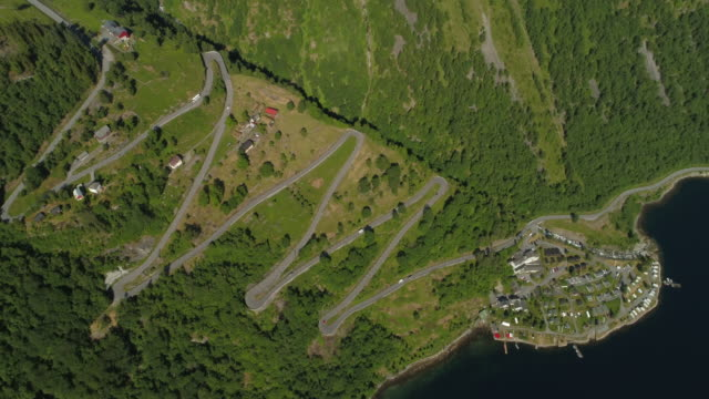 aerial: idyllic mountain with winding road by fjord during sunny day - geiranger fjord, norway - inlet stock videos & royalty-free footage