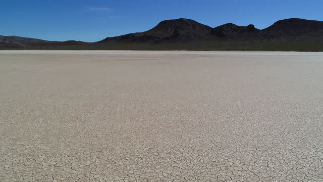 aerial: idyllic shot of arid desert against black mountain range on sunny day - winnemucca, nevada - nevada stock videos & royalty-free footage