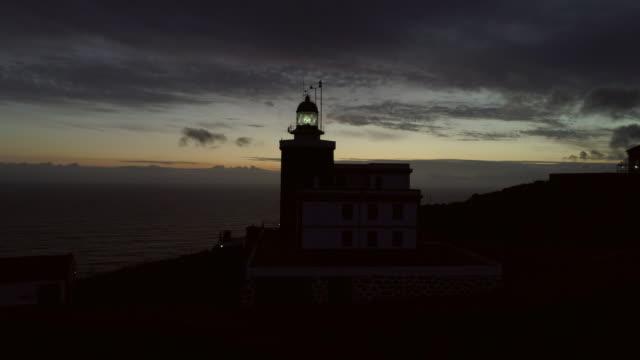 vídeos de stock e filmes b-roll de aerial: illuminated light in tower at cape finisterre lighthouse against sky during sunset - farol estrutura construída