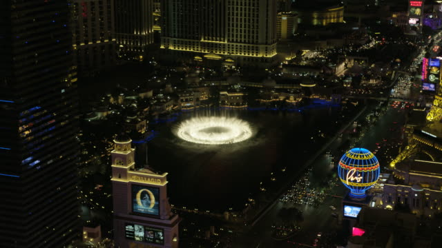 aerial illuminated night view las vegas bellagio fountains - replica della torre eiffel video stock e b–roll