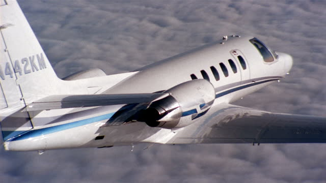 aerial jet flying over clouds / sun reflecting off tail of jet - private jet stock videos & royalty-free footage