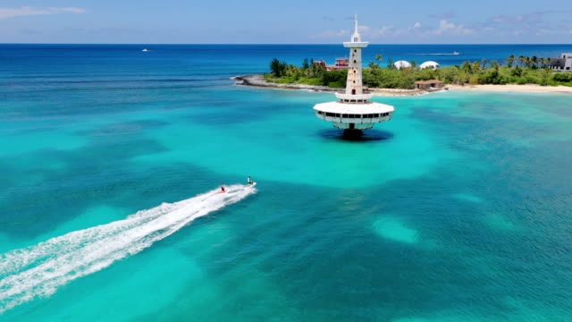 aerial: jet skiers riding near observation tower and peninsula in beautiful tropical water - nassau, bahamas - bahamas stock videos & royalty-free footage
