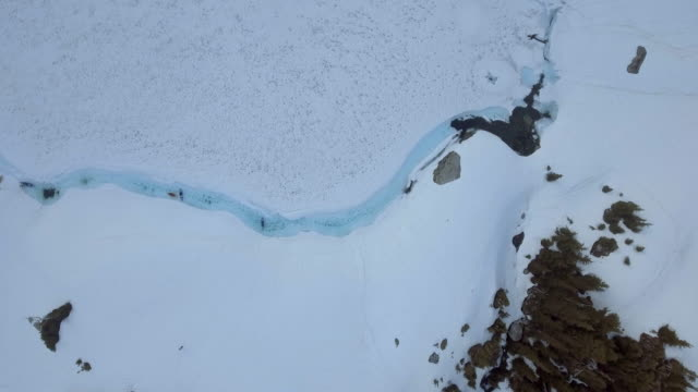 Aerial: Kayaks in Narrow Water at Edge of Frozen Lake in Vancouver, Canada