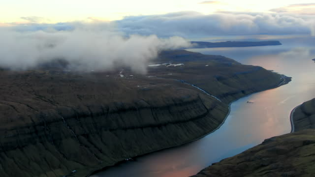 vídeos y material grabado en eventos de stock de aerial lake inlet flowing between rocky mountain faces, cloud cover above, streymoy island, faroe islands - erupcionar