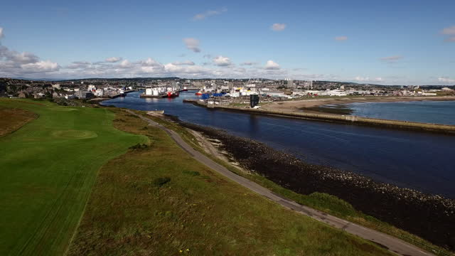aerial: large canal stretches to distant harbor and city spread across a long flat field towards low hills - aberdeen, scotland - barge stock videos & royalty-free footage