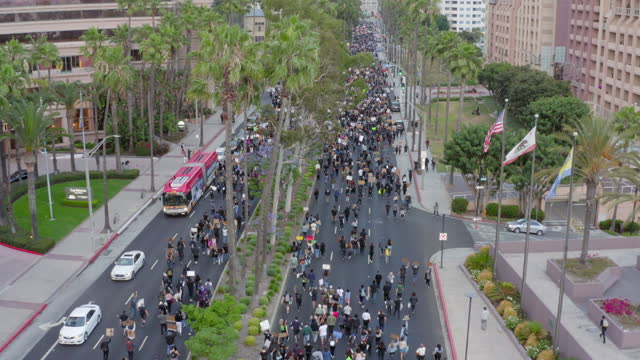 aerial: large crowd of protesters march down city street under buildings and trees - long beach, california - unfairness stock videos & royalty-free footage