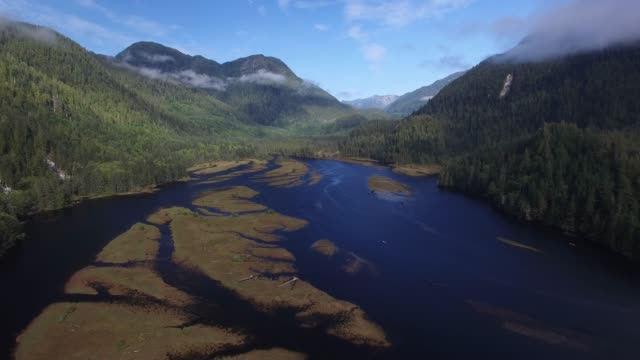 Aerial: Large River In Between Forest Covered Hills And Fog