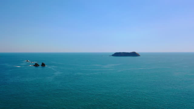 aerial: large rocks situated in beautiful blue ocean water  - playa espadilla, costa rica - clear sky stock videos & royalty-free footage