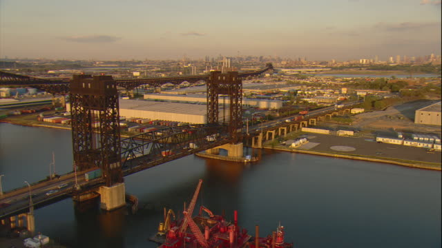 Aerial -Late afternoon orbiting view of old iron lift bridge and industrial warehouses in Kearny, NJ with the Manhattan skyline in the distance.