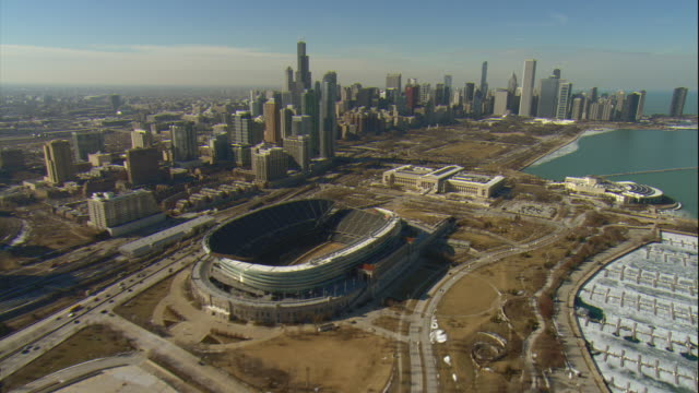 aerial -late winter afternoon shot of the chicago skyline passing soldier field and approaching the museum of natural history and shedd aquarium.  - shedd aquarium stock videos and b-roll footage