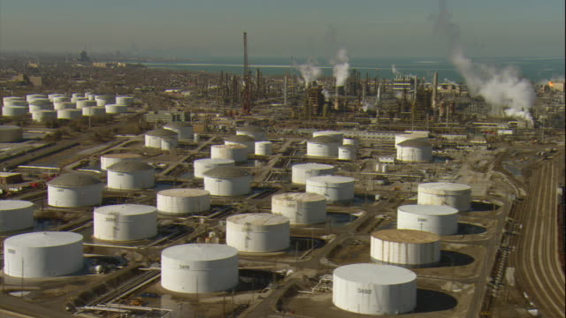 Aerial -Late winter afternoon side tracking shot of large tank farm and refinery in Whiting, IN, a suburb of Chicago.
