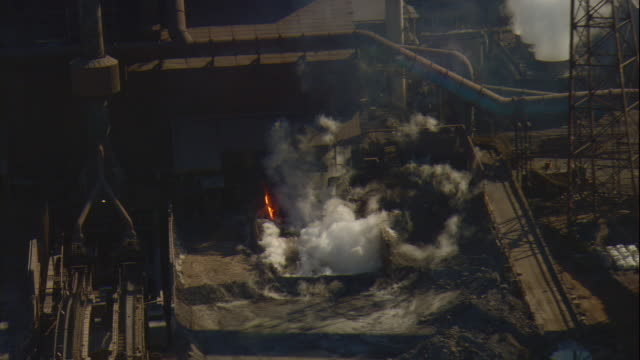 Aerial -Late winter afternoon tight shot of molten steel pouring out of steel mill at East Chicago, IN. Then a ZO to track across facility.