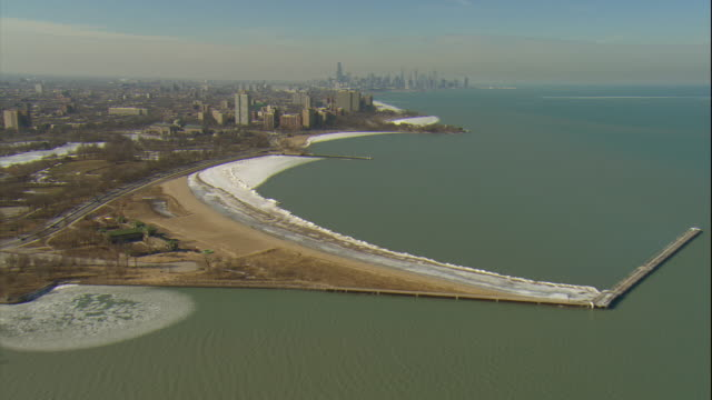 aerial -late winter afternoon wide shot of lake michigan shoreline at south chicago with chicago skyline in bg. - michigan stock videos and b-roll footage