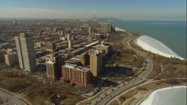 aerial -late winter afternoon wide view of lake michigan shoreline passing the museum of science & industry and promontory point park. - lago michigan video stock e b–roll