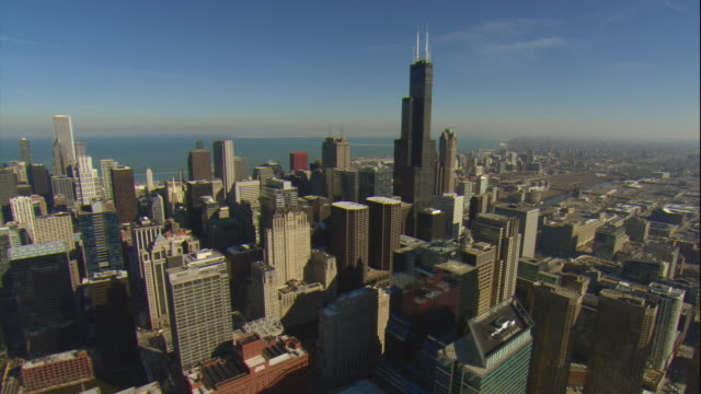 Aerial -Late winter afternoon wide view of the Chicago skyline with a slow ZI to upper levels of the Willis Tower.