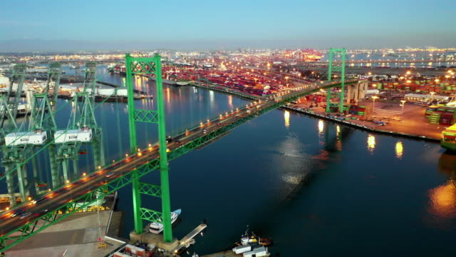 aerial left: bright green bridge bustling at night with boats all around in long beach, united states of america - long beach california video stock e b–roll