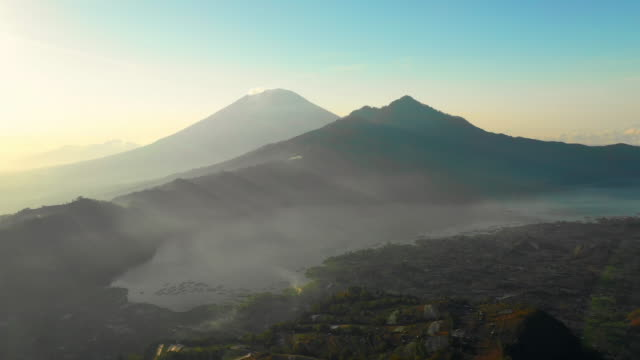 aerial left: dark, foggy mountains surrounded by lake and green plain - jatiluwih rice terrace, bali - rice terrace stock videos and b-roll footage