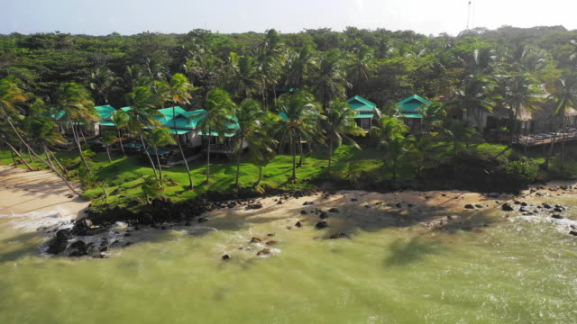 aerial left/spin right: buildings on shoreline of palm tree forest by ocean - little corn island, nicaragua - nicaragua stock videos & royalty-free footage
