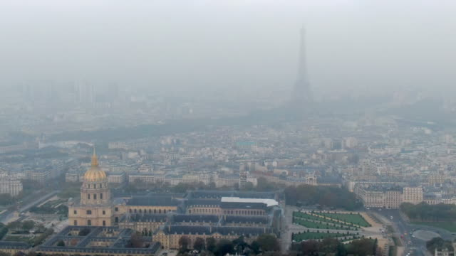 aerial: les invalides and surrounding city with hazy eiffel tower in paris, france - luftverschmutzung stock-videos und b-roll-filmmaterial