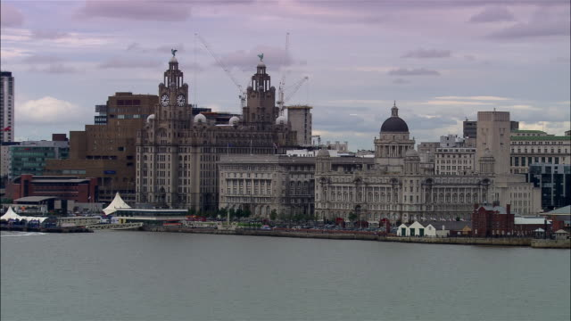 aerial liverpool waterfront with royal liver building and liverpool docks & harbour builing/ tilt down control tower and deck of freight ship/ liverpool, england - merseyside stock videos & royalty-free footage