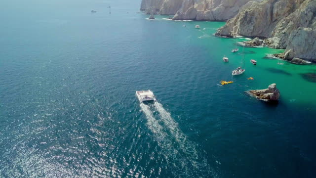 vídeos de stock e filmes b-roll de aerial lockdown: boat cruising rock cliffs in mexico - península de baixa califórnia