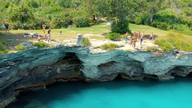 aerial lockdown: cliff jumping in the blue waters of bermuda in spanish point, bermuda - bermuda stock videos & royalty-free footage