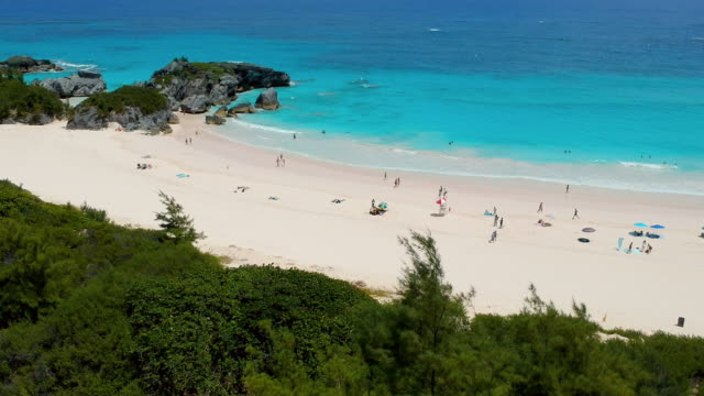 aerial lockdown: fun at the beach of bermuda on a summer day in spanish point, bermuda - bermuda stock videos & royalty-free footage