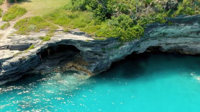 aerial lockdown: people walking down the cliff caves of bermuda in spanish point, bermuda - bermuda stock videos & royalty-free footage