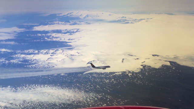 aerial lockdown: plane producing jet stream in the skies of greenland while showing mountains covered with snow - disko bay, greenland - wide stock-videos und b-roll-filmmaterial