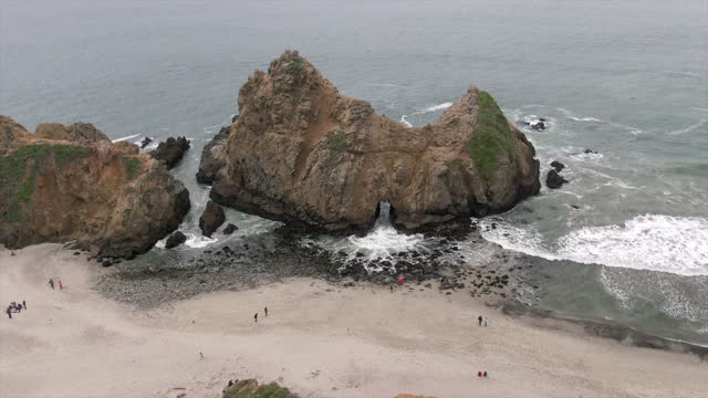 aerial lockdown shot of people by keyhole arch at pfeiffer beach, drone flying over famous natural landmark splashing waves - big sur, california - natural landmark stock videos & royalty-free footage