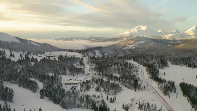 vidéos et rushes de aerial lockdown shot of snow covered forest by pathway, drone flying over vehicles against mountains - bend, oregon - vallée