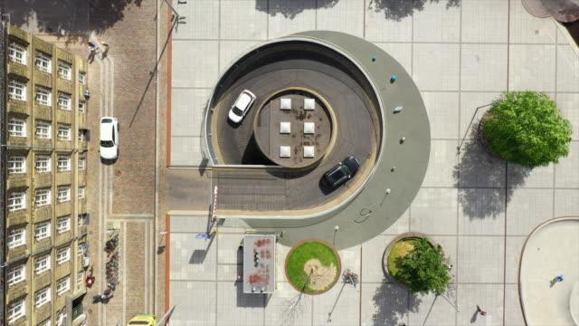 vídeos de stock e filmes b-roll de aerial lockdown shot of vehicles entering parking garage on sunny day, drone flying over people on footpath in city - copenhagen, denmark - parking