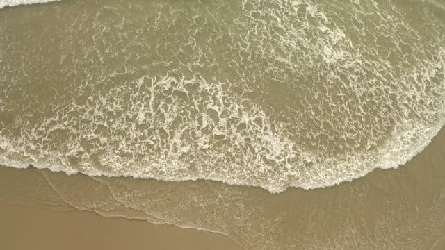 aerial lockdown shot of waves rushing towards coastline in sea - los angeles, california - tide stock videos & royalty-free footage