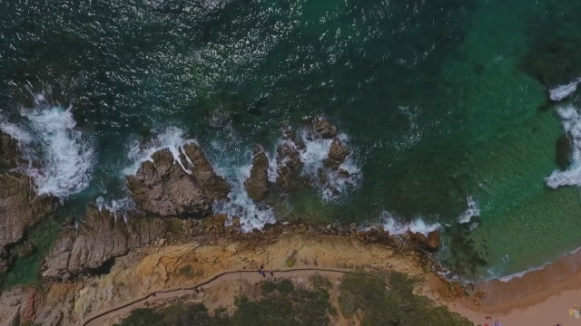 vidéos et rushes de aerial lockdown shot of waves splashing on rocks in sea during sunny day, drone ascending over rock formation - lloret de mar, spain - mar