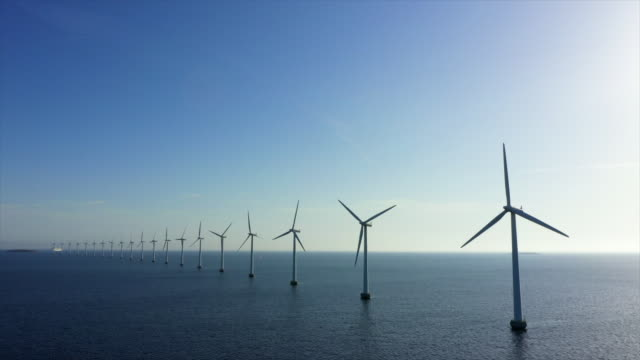 aerial lockdown shot of wind turbines in sea against blue sky, drone flying over water on sunny day - copenhagen, denmark - turbine stock videos & royalty-free footage