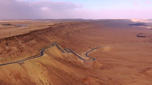 aerial: long road in middle of desert in negev desert, israel - negev stock videos & royalty-free footage