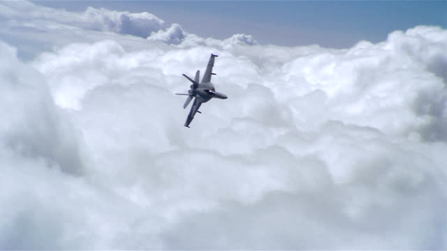 Aerial long shot F/A-18 Super Hornet soaring over clouds / turning / California