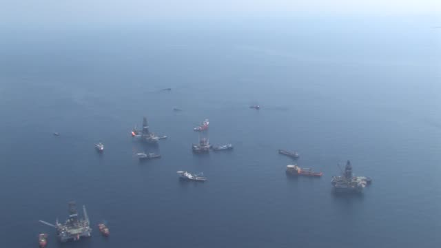 Aerial long shot of DeepWater Horizon oil spill recovery site Discoverer Enterprise and rigs drilling relief wells for BP oil spill patterns on water...