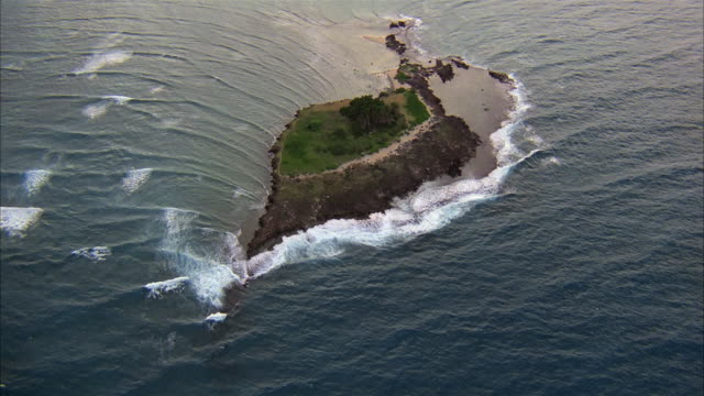 aerial long shot point of view deserted island with waves crashing onto shoreline - 無人島点の映像素材/bロール