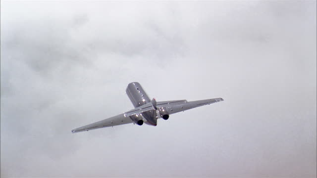 aerial long shot private jet flying through thick clouds - air to air shot stock videos and b-roll footage