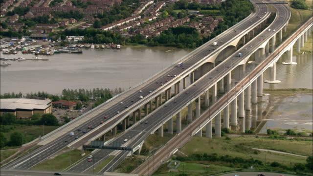 aerial long shot pulling back from m2 motorway and high speed railway crossing river medway / kent, england - kent england bildbanksvideor och videomaterial från bakom kulisserna