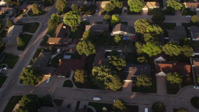 Aerial looking directly down upon a modest Midwest rural community, featuring rooftops, neighborhood homes, streets, trees and cul-de-sacs.