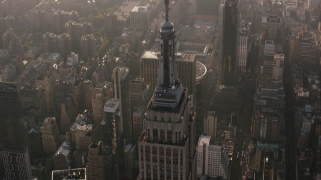 aerial looking down at buildings flying west over empire sate building, nyc - empire state building stock videos & royalty-free footage