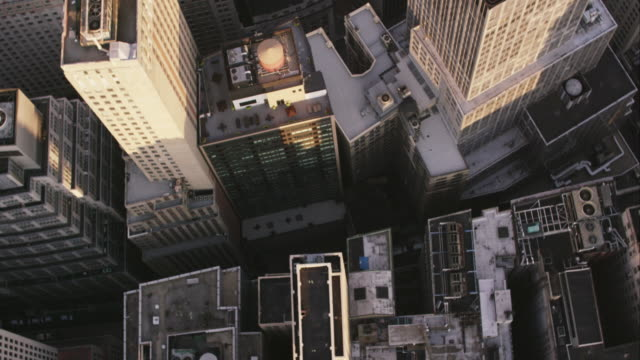 Aerial looking down at city buildings as camera turns to reveal more buildings, NYC