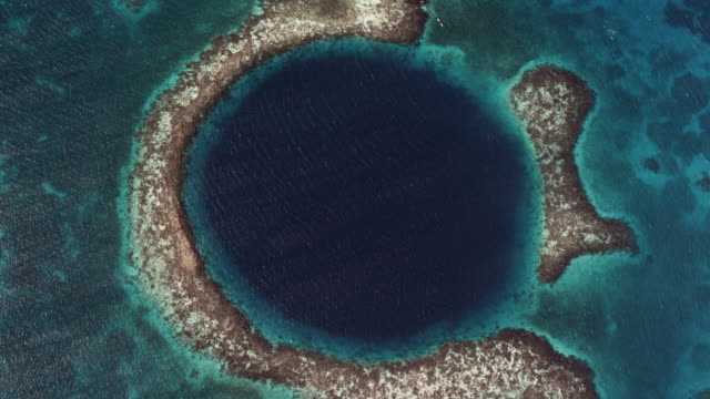 aerial looking down at great blue hole - riff stock-videos und b-roll-filmmaterial