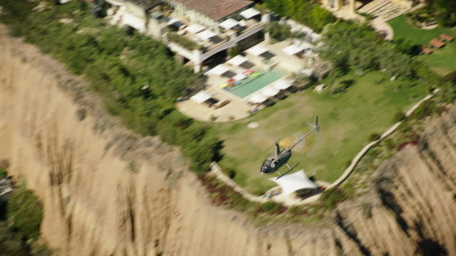 aerial, looking down from above, of robinson r44 helicopter flying along with trees and houses in the background, malibu, california, daytime. - malibu stock videos & royalty-free footage